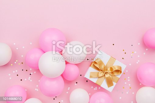 istock Gift or present box, balloons and confetti on pink pastel table top view. Flat lay for birthday or Mothers day. 1014668010