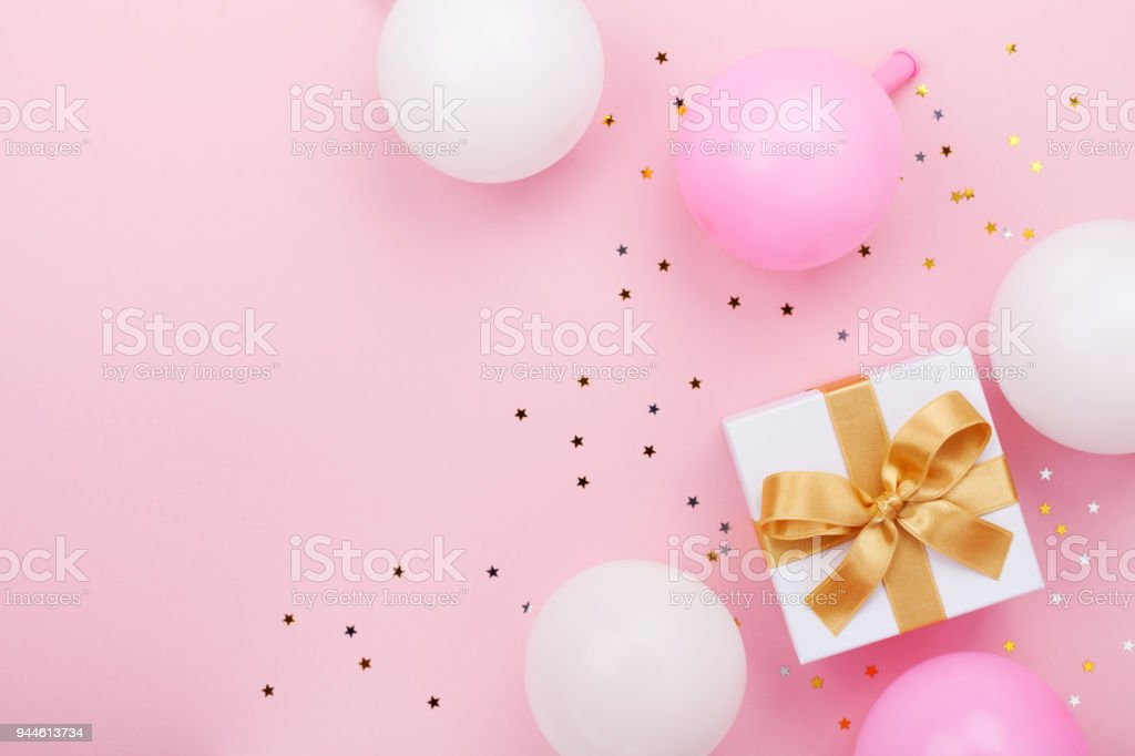 Gift or present box, balloons and confetti on pink table top view. Flat lay for birthday, mother day or wedding. stock photo