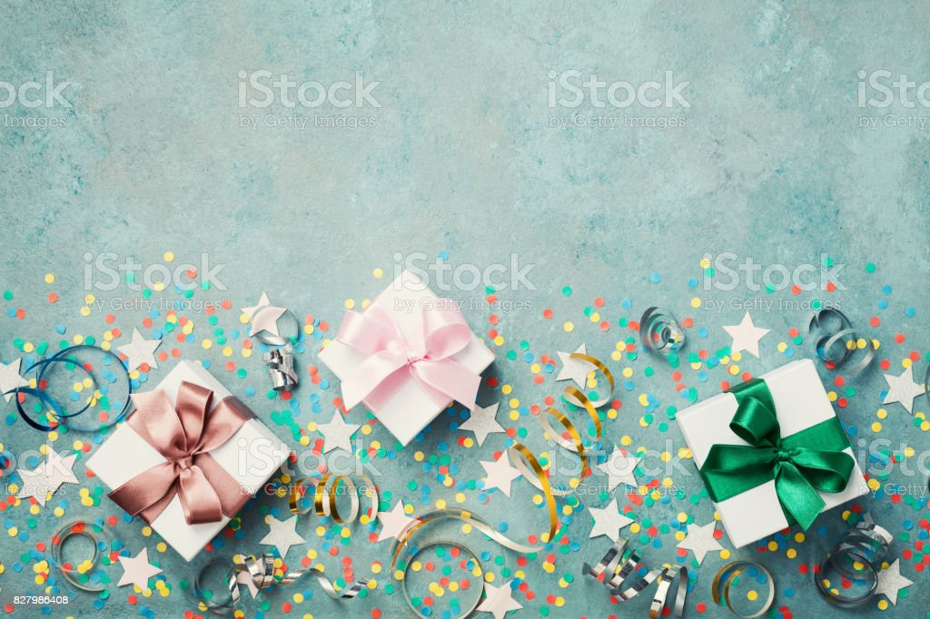 Gift or present box decorated colorful confetti and stars top view. Flat lay. Birthday background. Festive border with copy space. stock photo