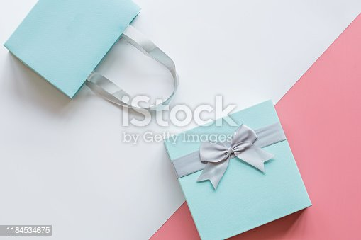 Gift or present box on pink table top view, overhead. Flat lay composition for birthday, mother day, 8 march, xmas, christmas, new year, valentine day or wedding. Holiday concept