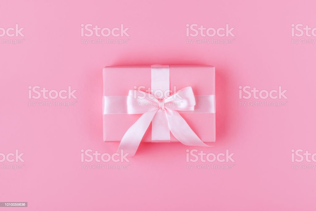 Gift or present box on pink table top view. stock photo