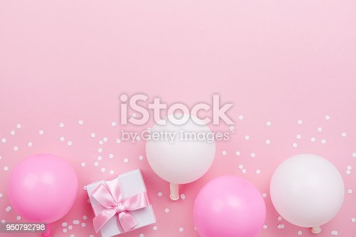 950793576 istock photo Gift or present box, pastel balloons and confetti on pink table top view. Flat lay composition for birthday, mother day or wedding. 950792798