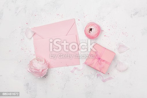 825251738istockphoto Gift or present box, pink paper blank and ranunculus flowers. Greeting mockup concept. Flat lay. 680461672