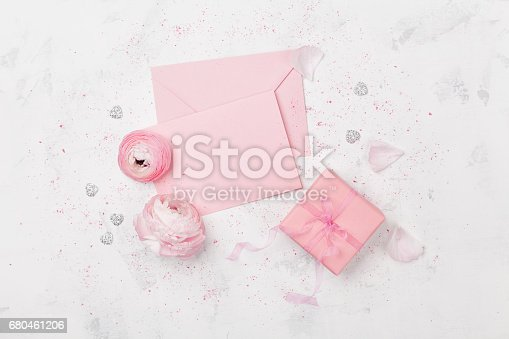 825251738istockphoto Gift or present box, pink paper blank decorated ranunculus flowers. Greeting mockup concept. Flat lay. 680461206