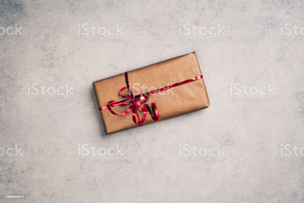Gift or present in brown paper box with red ribbon, above view. Top...