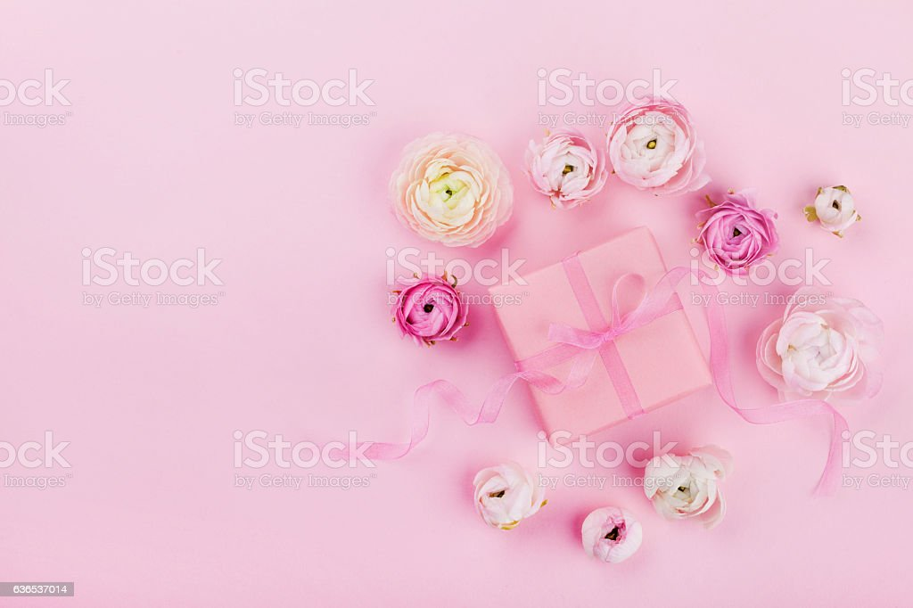 Gift or present box and beautiful flower on pink desk from above for...