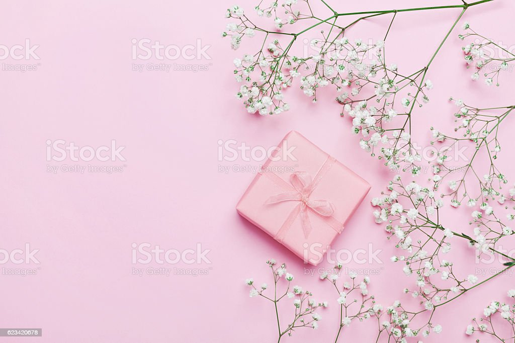 Gift or present with flowers on pink table. Flat lay.