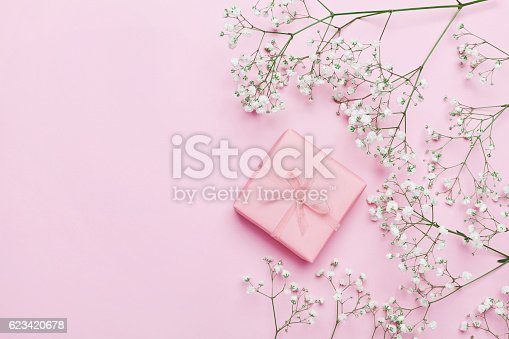 istock Gift or present with flowers on pink table. Flat lay. 623420678