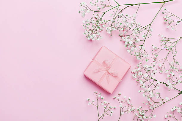 Gift or present with flowers on pink table. Flat lay. stock photo
