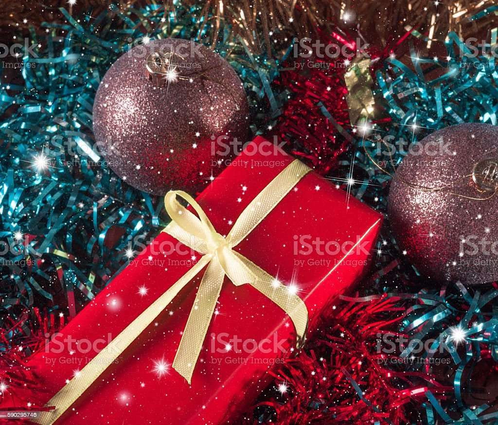Gift packaging among Christmas tinsel, royaltyfri bildbanksbilder