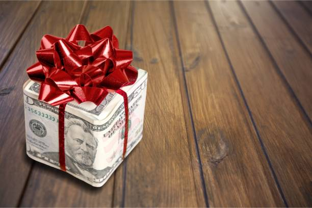 Gift. Christmas present with red bow wrapped in dollar banknotes isolated on white background commercial activity stock pictures, royalty-free photos & images