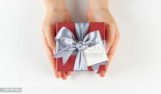 Top view of woman hand holding red gift box. Isolated on white background.