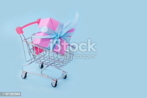 Gift pink box with blue satin ribbon in shopping cart on blue background, congratulations on Women's Day, mum's day, Valentine's day, happy birthday, Christmas