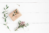 Gift, pink flowers and eucalyptus branches on white wooden background