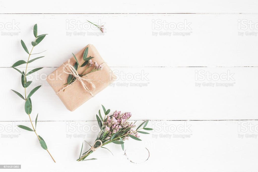Gift, pink flowers and eucalyptus branches on white wooden background stock photo