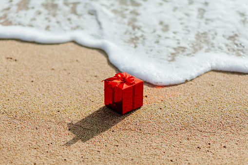 present gift in red box  on the beach in tropics. Present red box flowing in the sea. christmas holideys on the beach