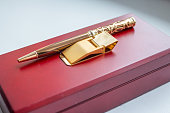 gift set. holder clip for money. stationery. wooden present box. golden money clip. A pen in a gift box isolated on white.fountain pen in wooden case made of mahogany, business concept