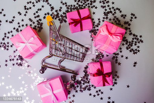 Gift shopping, shopping cart is full of gift boxes. New year's shopping concept. Pink boxes, trolley with gifts, top view. grey background and shiny confetti