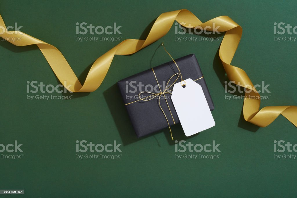 Gift tag, Christmas gifts and gold ribbon on dark green background, flat lay stock photo
