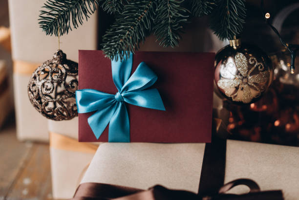 Gift voucher in burgundy envelope with blue bow under the Christmas tree. Christmas gift Gift voucher in burgundy envelope with blue bow under the Christmas tree. Christmas gift gift card stock pictures, royalty-free photos & images