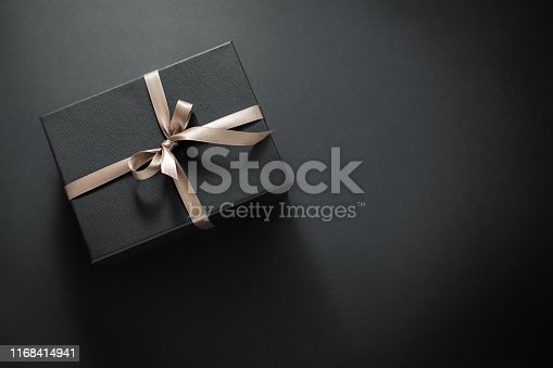 istock Gift wrapped in dark paper on dark background 1168414941