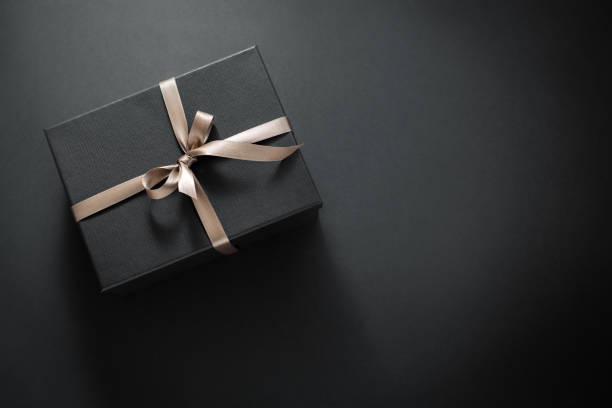 Gift wrapped in dark paper on dark background One gift wrapped in dark black paper with luxury bow on dark background. Horizontal with copy space. gift box stock pictures, royalty-free photos & images