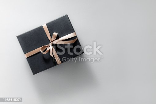 istock Gift wrapped in dark paper on grey background 1168415074