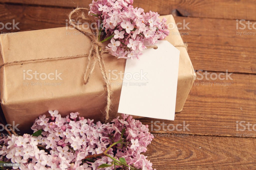 Gift wrapped with kraft paper on a wooden table, tied with a rope, with a bouquet of pink lilac stock photo