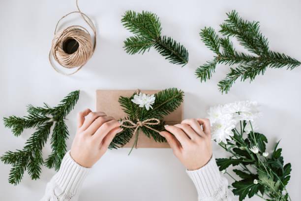 geschenkverpackung mit naturpapier, tanne und weiße blume. - eco bastelarbeiten stock-fotos und bilder