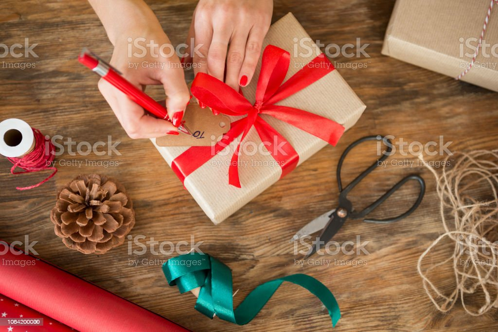 Christmas Gift Wrapping Station.Diy Gift Wrapping Woman Filling Out Christmas Gift Tag On Rustic Wooden Table Overhead View Of Christmas Wrapping Station Stock Photo Download Image