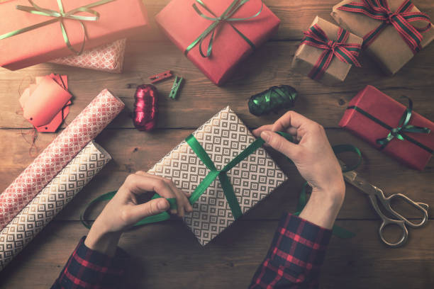 gift wrapping. woman tie a ribbon bow stock photo