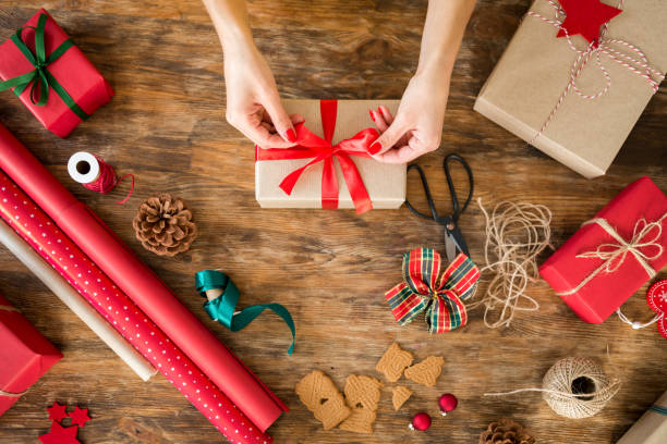 diy gift wrapping. woman wrapping beautiful christmas gifts on rustic wooden table. overhead view of christmas wrapping station. - avvolto foto e immagini stock