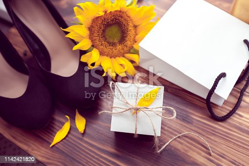 gift with white package, black heels shoes and yellow sunflowers