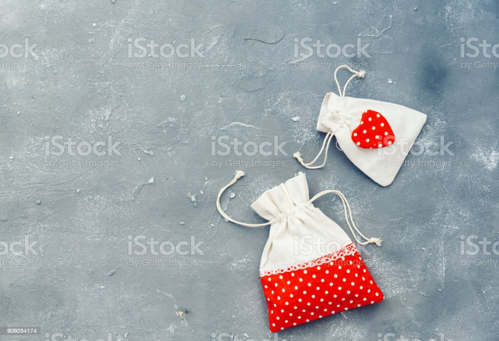 Gifting theme image with a checkered fabric pouch and a decorative red heart over vintage background stock photo