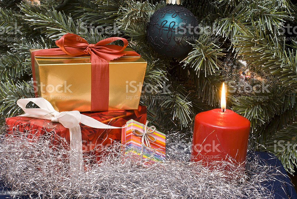 Gifts and candle under a Christmas tree royalty-free stock photo