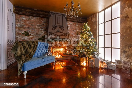 istock gifts at the Christmas tree. Christmas evening by candlelight. classic apartments with a fireplace. 1076192036