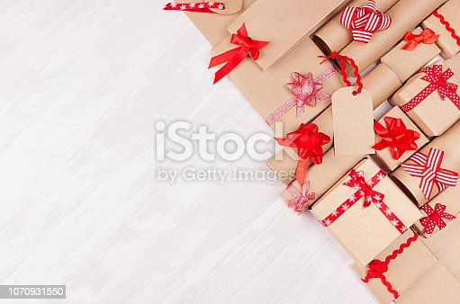 istock Gifts background for design advertising - set of craft paper presents with red bows, blank label on white wood board, top view, copy space. 1070931550