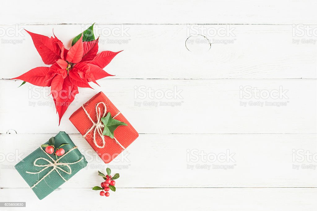 Gifts, fir branches, christmas poinsettia. Flat lay, top view stock photo