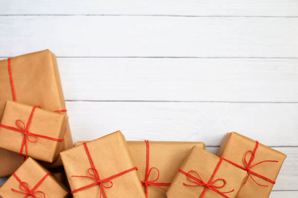 Gifts for friends and family. Heap of boxes. Selection of presents in handcrafted paper packaging and red twine bows. stock photo
