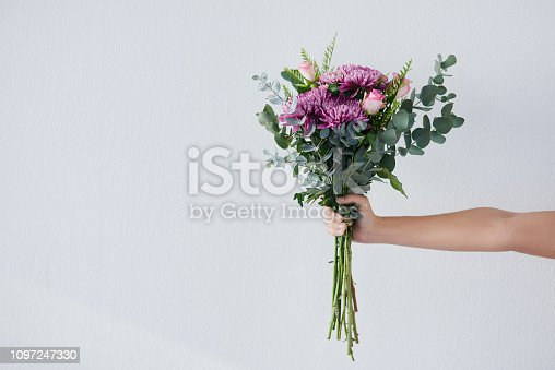 Studio shot of an unrecognizable woman holding a bunch of flowers against a grey background