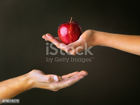 Cropped studio shot of a woman offering a man a red apple against a dark background