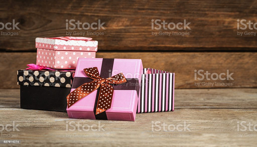 Gifts in beautiful boxes on a wooden surface stock photo