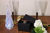 istock Gifts of watch in box and champagne glass and christmas tree on the table 1044353488