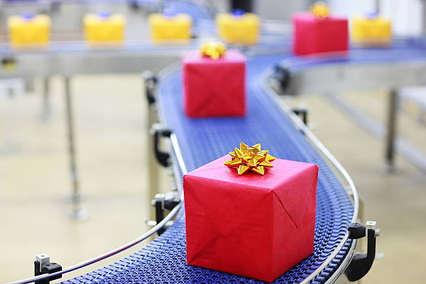 Gifts on conveyor belt in Christmas presents factory stock photo