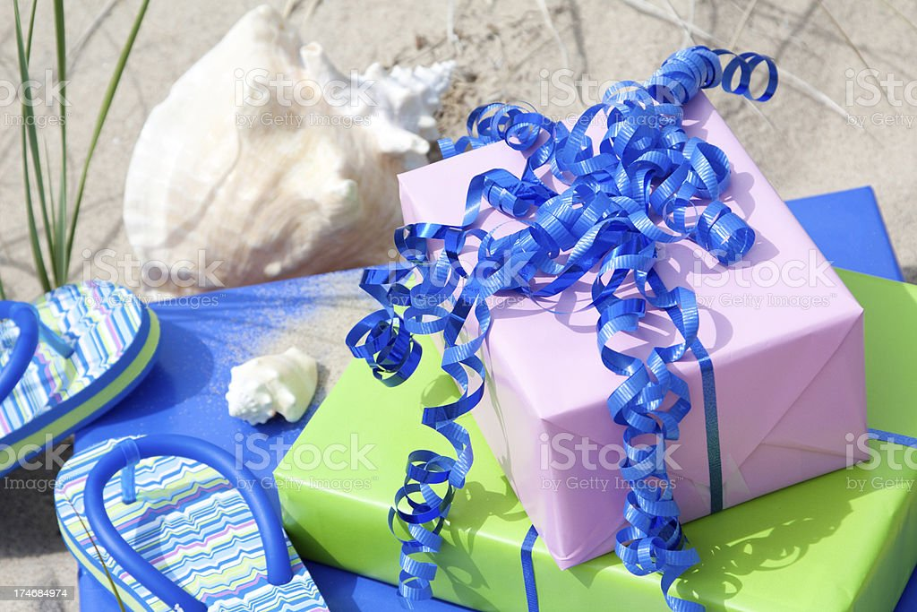 \'Pastel colored gifts, sea shells and flip flops on a warm beach.\'