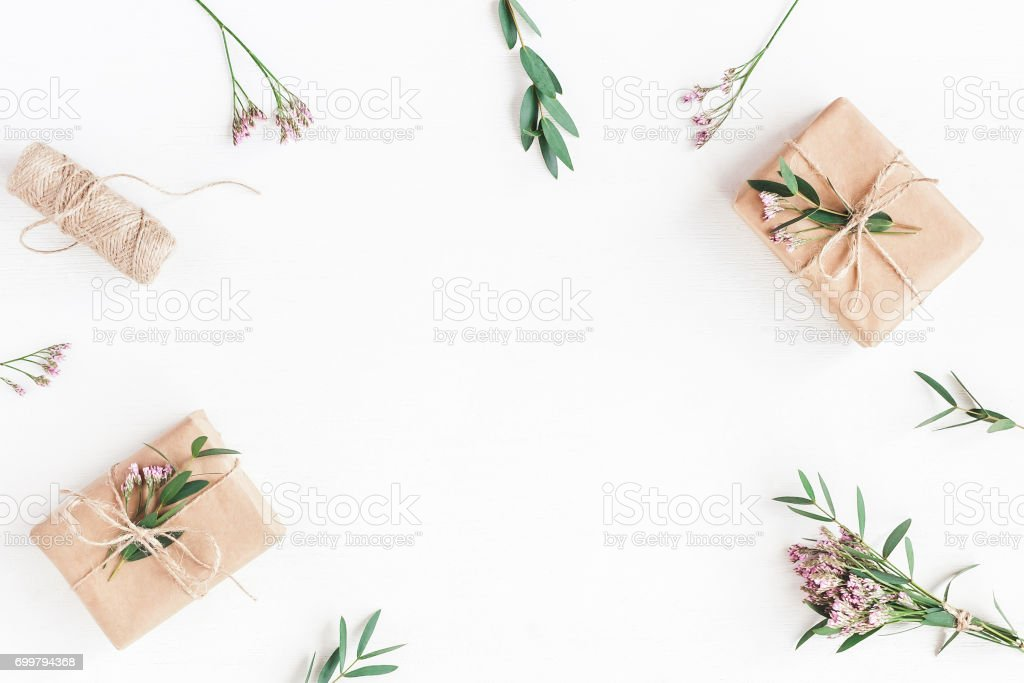 Gifts, pink flowers and eucalyptus branches. Flat lay, top view stock photo