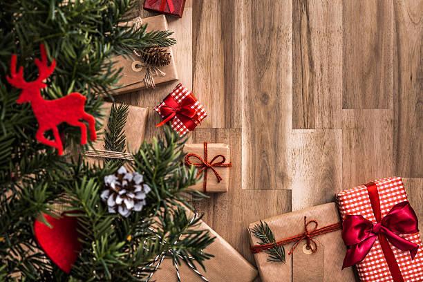 gifts under christmas tree over wooden floor. top view. - weihnachtsideen stock-fotos und bilder