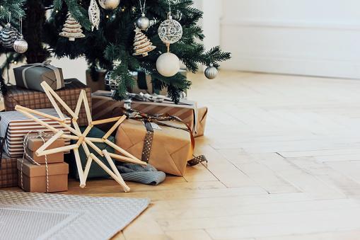 Gifts under decorated Christmas tree, minimalistic Scandinavian decor background