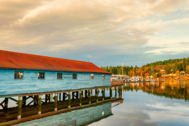 Gig Harbor Washington Skansie netshed reflects in the still waters of the Puget Sound while leading the eye to the opposite shore lined with residential home in Gig Harbor, Washington. gig harbor stock pictures, royalty-free photos & images