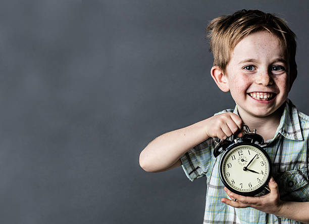giggling young child showing retro alarm clock for time concept – Foto